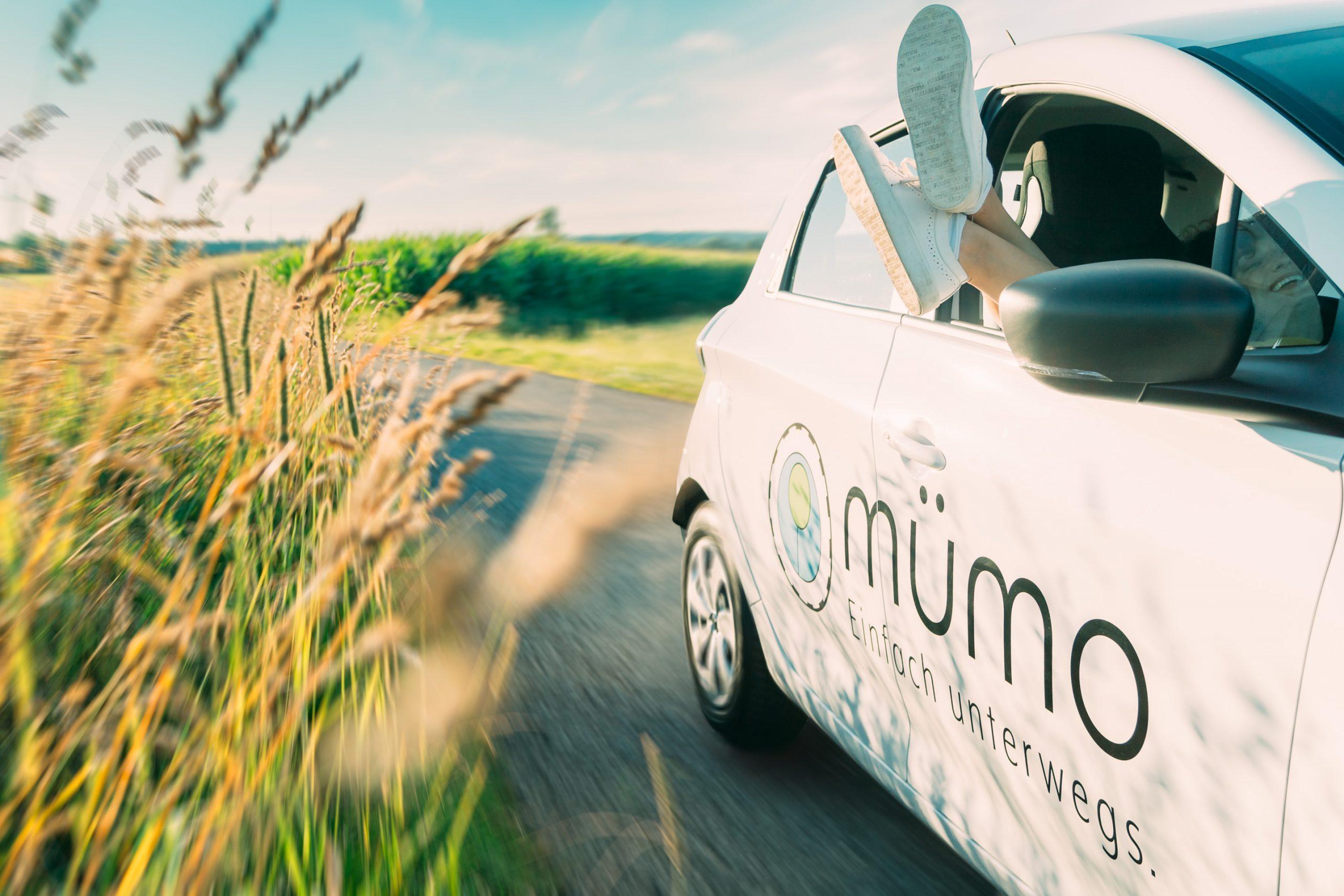 auf der Teerstraße im Feld mit dem Renault Zoe die Füße aus dem Beifahrerfenster Grinsen mit Motion Blur