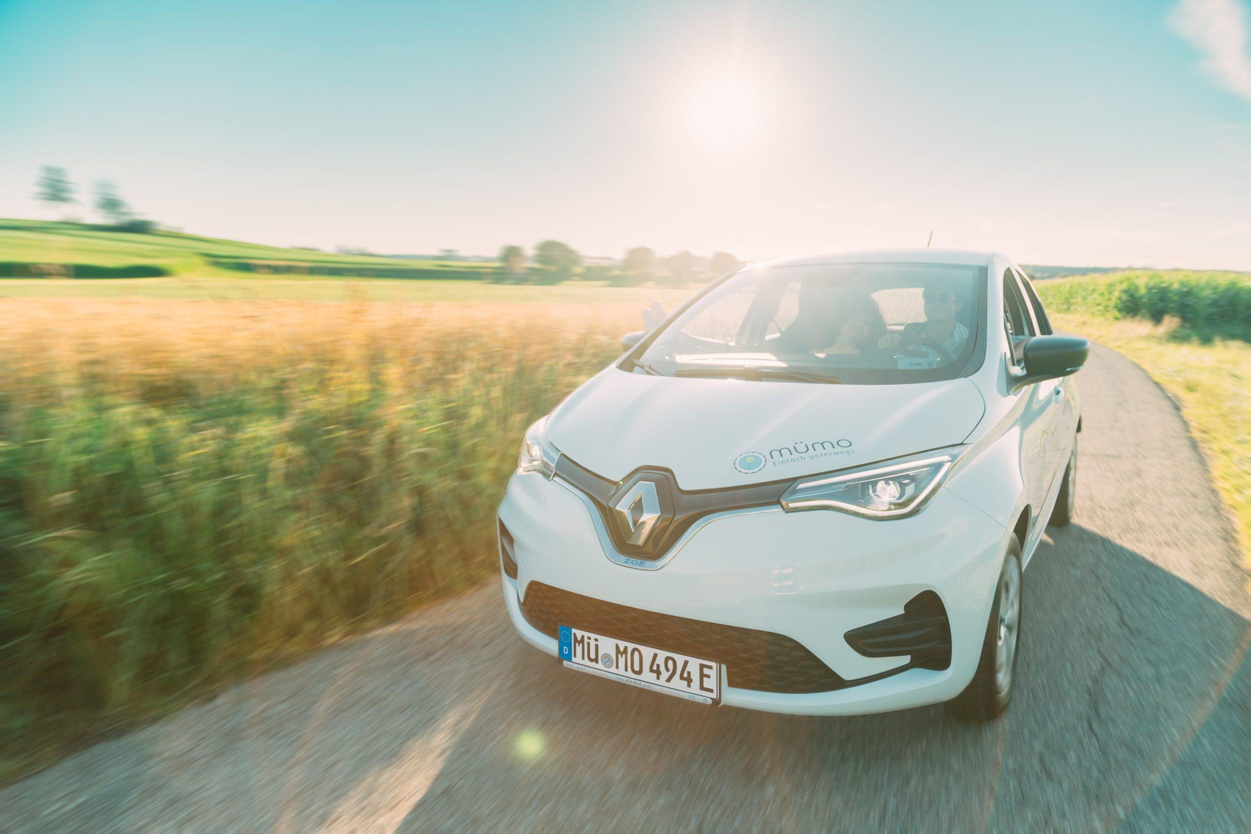 Pärchen im Renault Zoe auf Teerstraße im Feld mit Motion Blur bei Sonnenuntergang