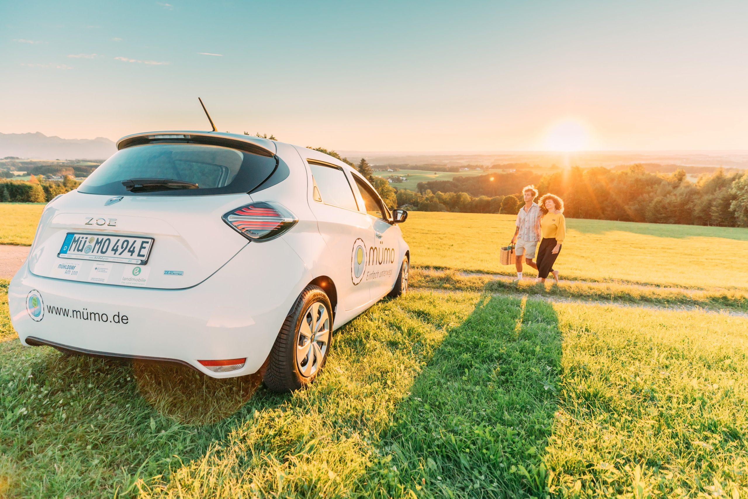 vom Picknick im Sonnenuntergang geht das Pärchen zurück zum Auto Renault Zoe