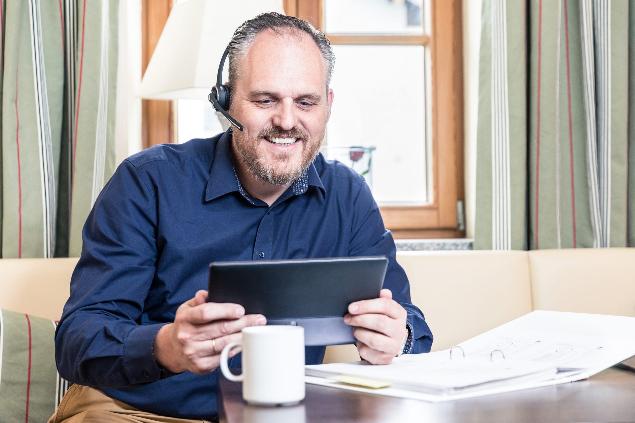 Bestager hat grinsend Spaß am E-Learning Onlineseminar mit Videotelefonie, Tablet, Ordner, Kaffeetasse und Headset vor Fenster