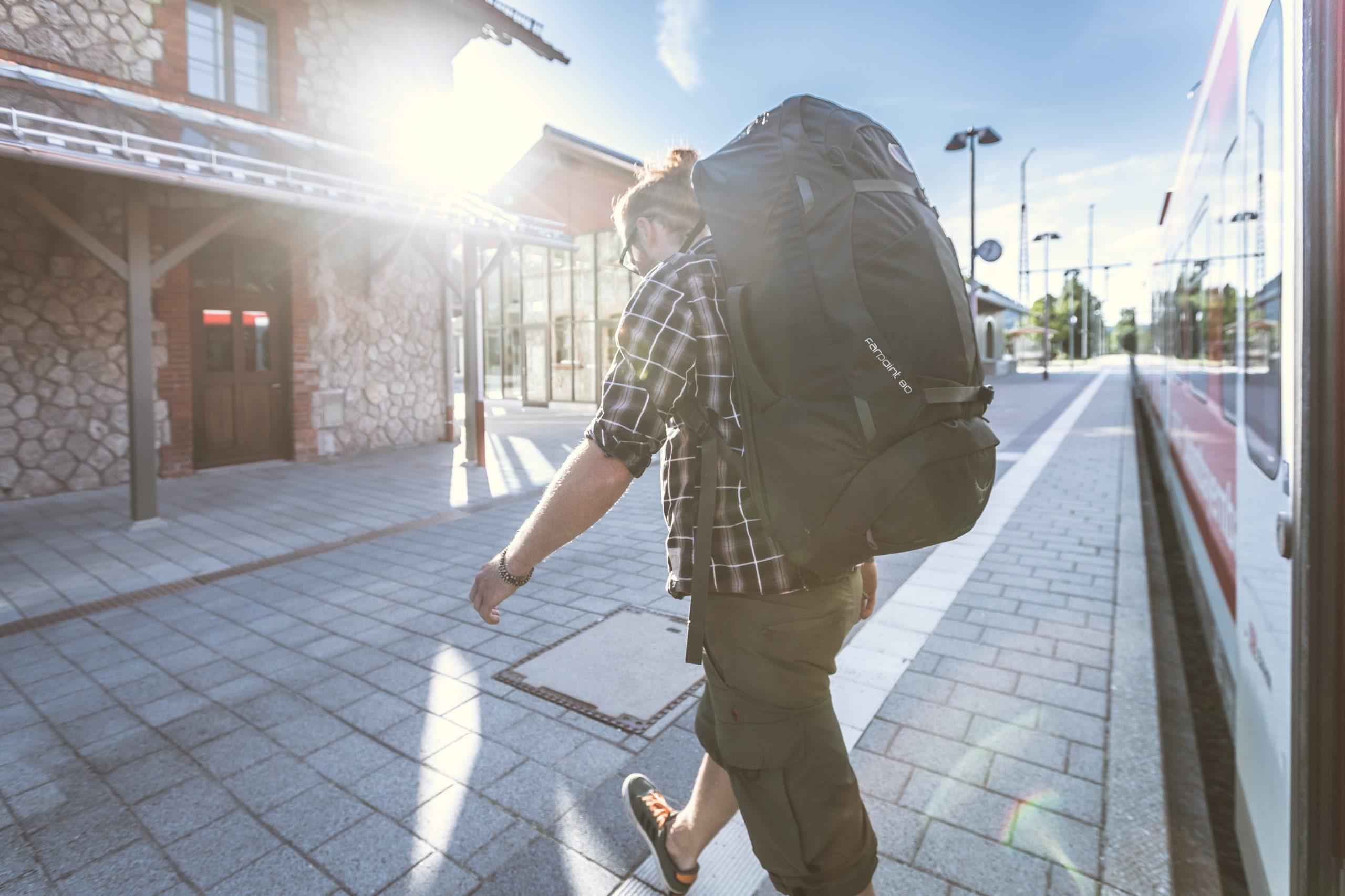 männlicher Backpacker mit Osprey Farpoint 80 Rucksack verlässt den Regionalzug am Bahnhof im Sonnenuntergang