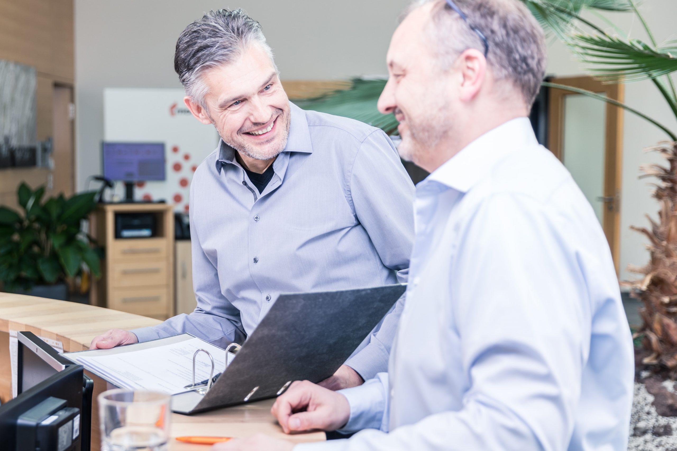Kollegen männlich im Gespräche mit Ordner Grinsen Business Portrait