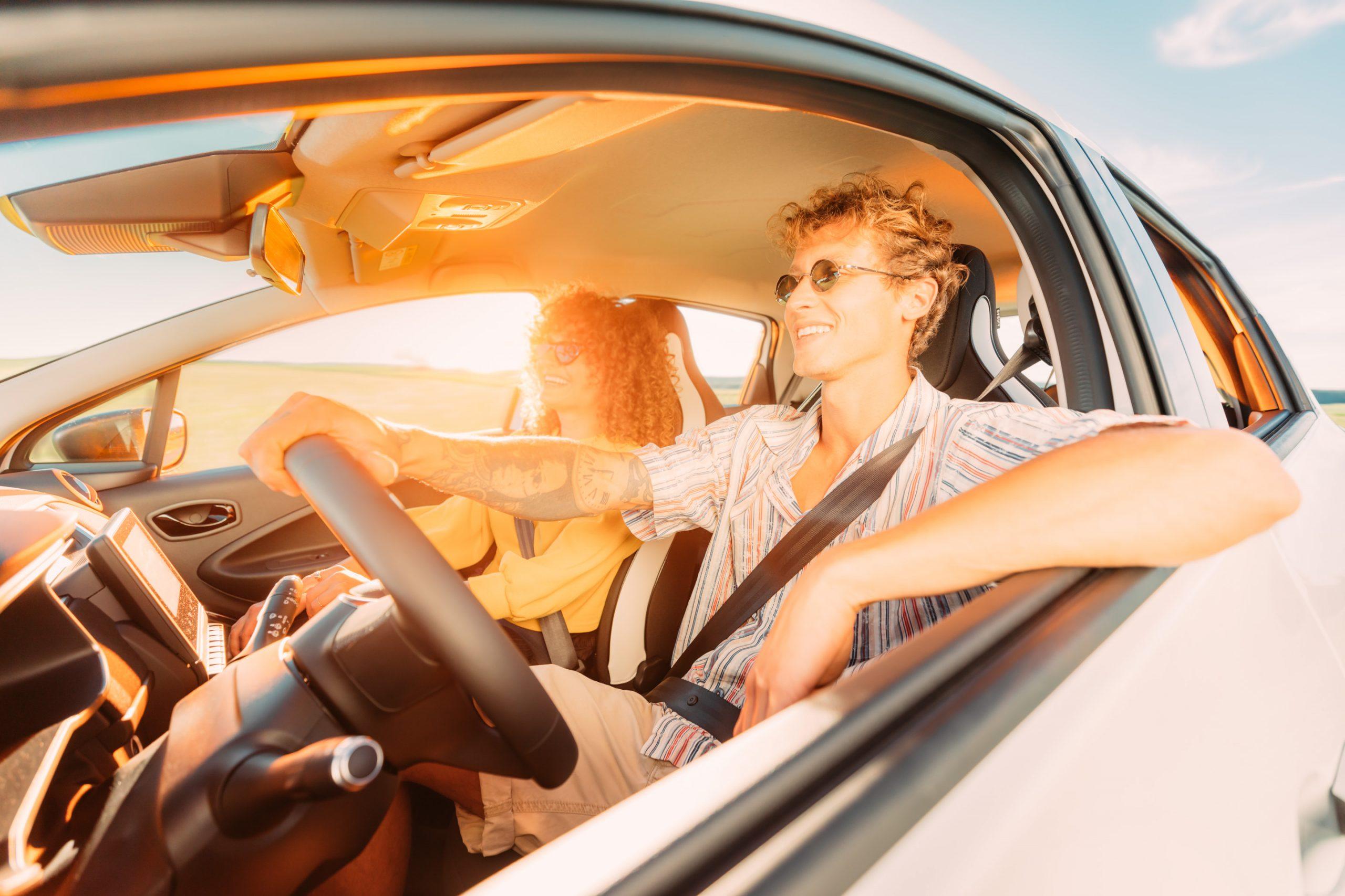 Pärchen fährt über Land grinsend in den Urlaub bei Sonnenuntergang durchs Fenster des Renault Zoe