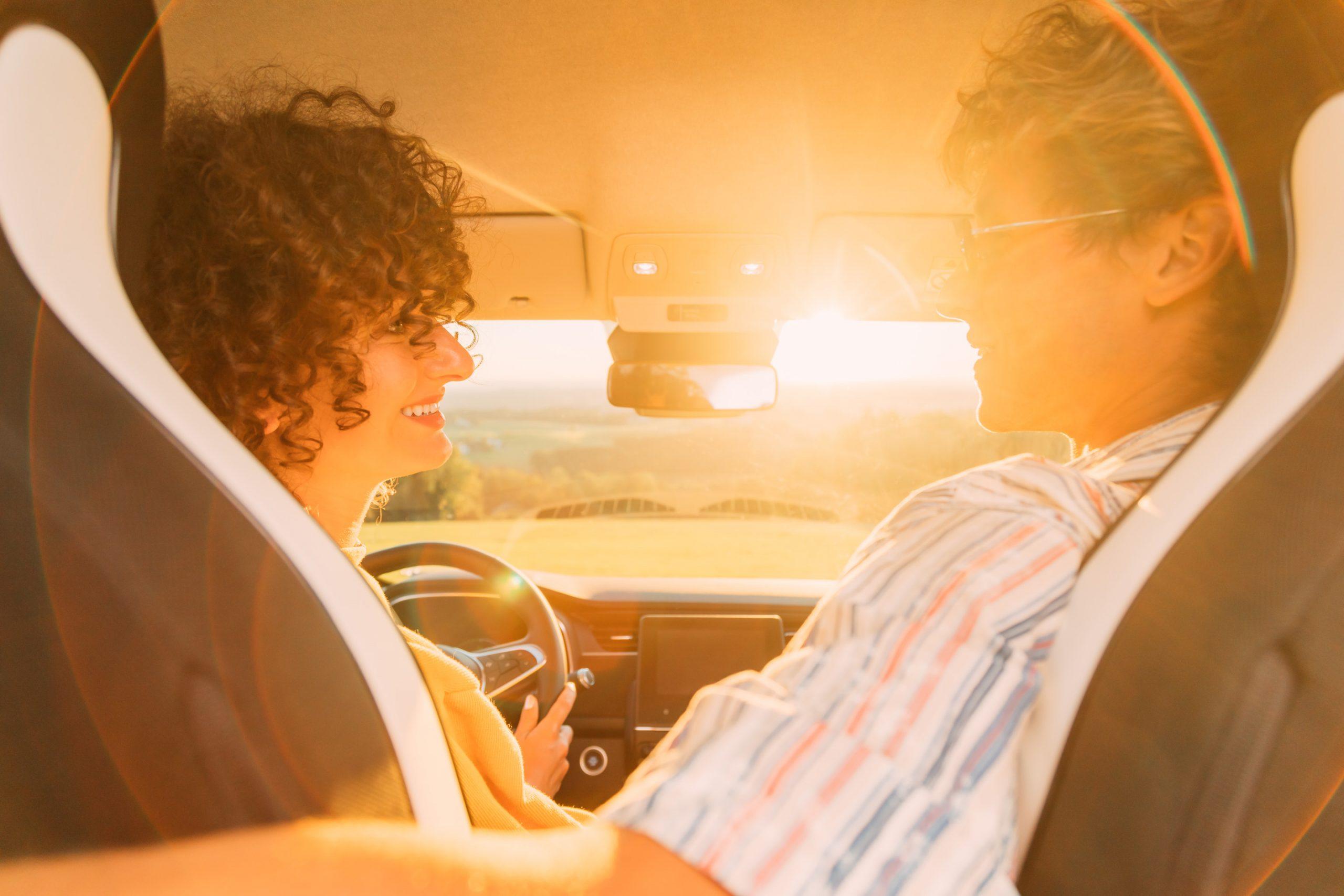 Pärchen genießt ginsend den Sonnenuntergang auf dem Vordersitz des Renault Zoe